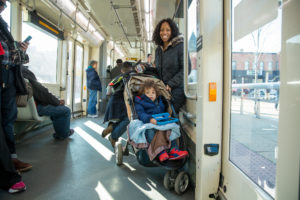 passenger on DC Streetcar stands with their child in a stroller